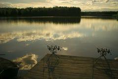 Pesca di sera Canne da pesca sul pilastro di legno sullo stagno Fotografia Stock Libera da Diritti