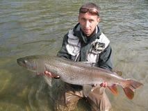 Pesca di Taimen Immagine Stock