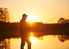 Pesca di tramonto pescatore con la barretta di filatura immagini stock libere da diritti