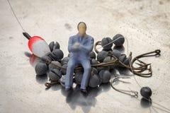 Pesca diminuta do homem de negócios do brinquedo dos povos Foto de Stock