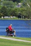 Pesca disabile dell'uomo in un lago fotografia stock libera da diritti
