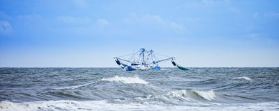 Pesca do barco de pesca em mares ásperos imagens de stock