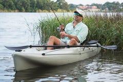Pesca do caiaque do homem na água pouco profunda gramínea Imagem de Stock