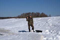Pesca do gelo do inverno, um pescador na roupa morna que pesca no furo - Rússia Berezniki 7 de abril de 2018 fotos de stock royalty free