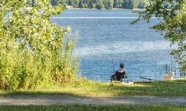 A pesca do homem com é cão Imagens de Stock