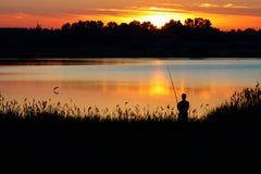 Pesca do homem com uma haste no por do sol Foto de Stock Royalty Free