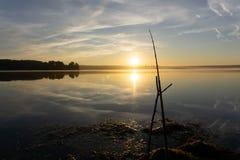 Pesca do homem de Fisher com haste de giro em um banco de rio no nascer do sol nevoento enevoado imagens de stock