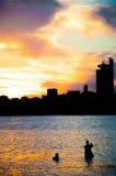 Pesca do homem de Fisher em um rio no por do sol Imagens de Stock Royalty Free