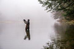 Pesca do homem em um rio imagem de stock royalty free