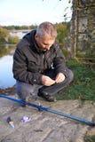 Pesca do homem em uma lagoa Fotografia de Stock