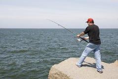 Pesca do homem em uma rocha Fotos de Stock Royalty Free