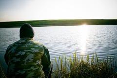 Pesca do homem na costa do lago foto de stock royalty free