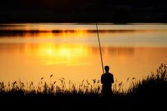 Pesca do homem no por do sol Fotos de Stock
