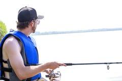 Pesca do homem novo em um lago Imagens de Stock Royalty Free