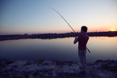 Pesca do homem novo na lagoa e no passatempo da apreciação Foto de Stock Royalty Free