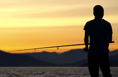 Pesca do homem novo no crepúsculo em Vancôver Foto de Stock Royalty Free