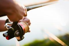 Pesca do homem novo no lago no por do sol que aprecia o passatempo Imagem de Stock