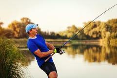 Pesca do homem novo no rio no por do sol Fiserman entusiasmado feliz que puxa a haste com peixes imagem de stock