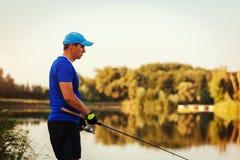 Pesca do homem novo no rio do verão no por do sol Virada triste do fiserman devido à captura má fotografia de stock royalty free