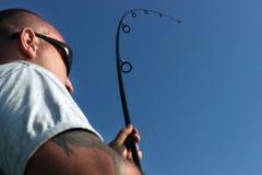 Pesca do homem novo, pescador que guarda a haste na ação Foto de Stock