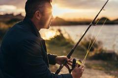 Pesca do homem perto de um lago fotografia de stock