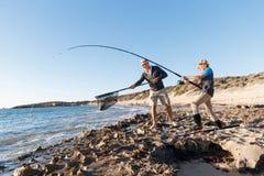 Pesca do homem superior com seu neto Fotografia de Stock Royalty Free