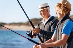 Pesca do homem superior com seu neto Imagens de Stock Royalty Free