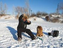 Pesca do inverno com um cão Fotografia de Stock
