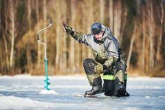 Pesca do inverno no gelo Pescador que engancha peixes morder fotografia de stock royalty free
