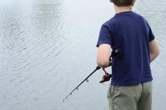 Pesca do menino na represa ou no lago baixo Foto de Stock