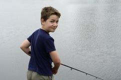 Pesca do menino no lago baixo Imagem de Stock
