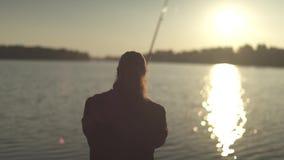 Pesca do pescador com uma vara de pesca no fundo do rio durante o por do sol Fisher gerencie a bobina em um gerencio filme