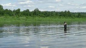Pesca do pescador em um rio calmo na manhã Homem nas artes de pesca que stending em um rio e em lances um polo de pesca filme