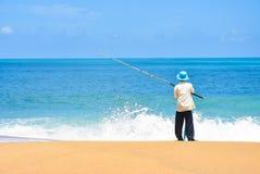 Pesca do pescador na praia e na onda do mar, céu azul com pesca do pescador da vara de pesca nos peixes bonitos do homem do seasc Fotos de Stock