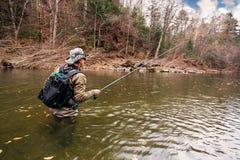 A pesca do pescador no rio está esperando a captura Foto de Stock
