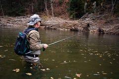 A pesca do pescador no rio está esperando a captura fotografia de stock royalty free