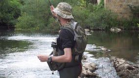 Pesca do pescador no rio, guardando a vara de pesca filme