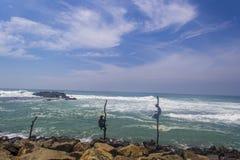 Pesca do pescador do pernas de pau na praia imagens de stock