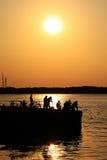 Pesca durante la puesta del sol Imagenes de archivo