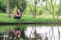 Pesca e relaxamento da mulher, agachados na frente de um lago, guardando imagens de stock royalty free