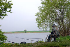 Pesca em um lago no mau tempo Imagens de Stock
