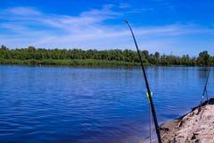 Pesca en el alimentador en la orilla de un río hermoso Fotos de archivo libres de regalías