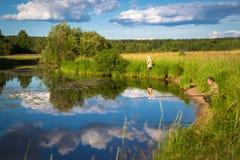 Pesca en el lago con los lirios en la ubicación rural Imagenes de archivo