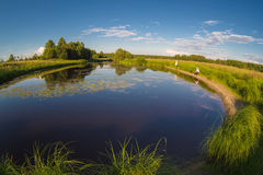 Pesca en el lago con los lirios en la ubicación rural Fotografía de archivo