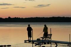 Pesca en el lago en la puesta del sol Fotos de archivo libres de regalías