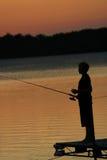 Pesca en el lago en la puesta del sol foto de archivo