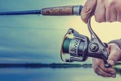 Pesca en el lago en la puesta del sol Imagenes de archivo