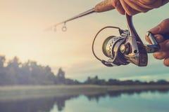 Pesca en el lago en la puesta del sol Fotos de archivo