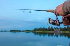 Pesca en el lago en la puesta del sol Imagen de archivo libre de regalías