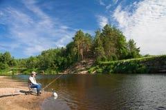 Pesca en el río en un lugar rural en un día de verano Foto de archivo libre de regalías